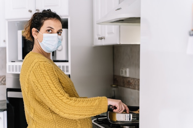 Mulher grávida em um suéter amarelo cozinhar em pé em uma cozinha com uma máscara no rosto