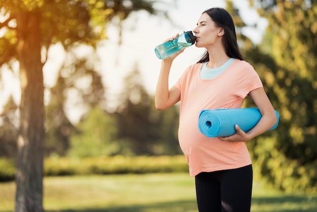 Mulher grávida em uma camiseta rosa está de pé no parque.