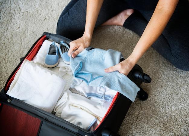Mulher grávida embalagem coisas de bebê para o hospital