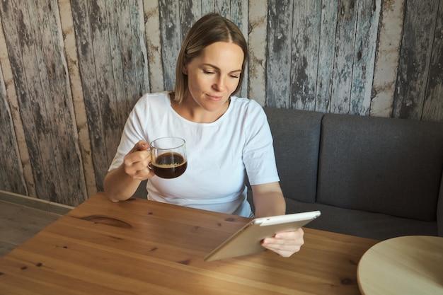 Mulher grávida encantadora bebe um café e olhando para a tela de um tablet de computador. gravidez e tecnologia, conceito de compra online.