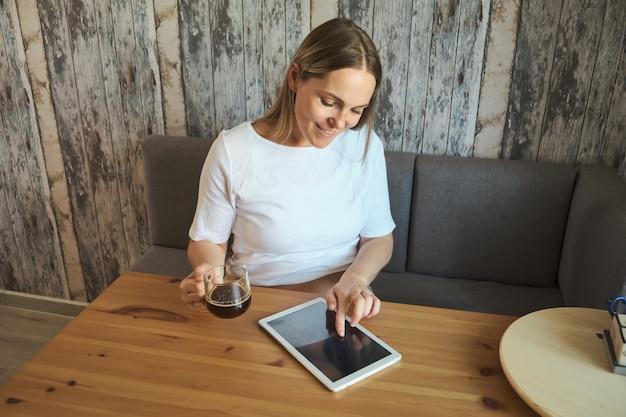 Mulher grávida encantadora bebe uma bebida e olha para a tela de um tablet.
