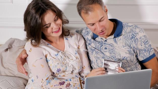 Mulher grávida encantadora com homem sentado com papel fetal escasso e laptop animado com o parto