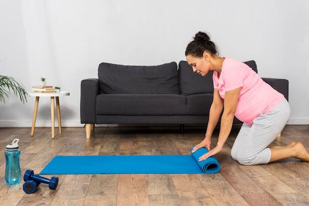 Mulher grávida enrolando tapete de ginástica em casa