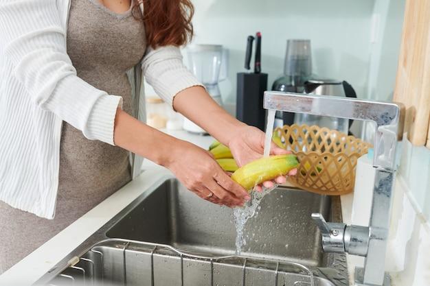 Mulher grávida enxaguando bananas