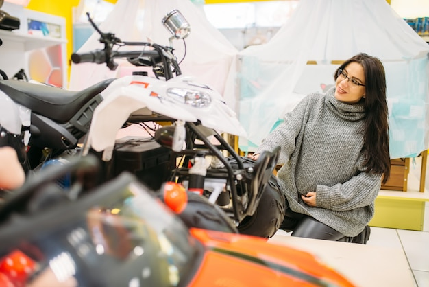 Mulher grávida escolhendo carro elétrico em loja de brinquedos