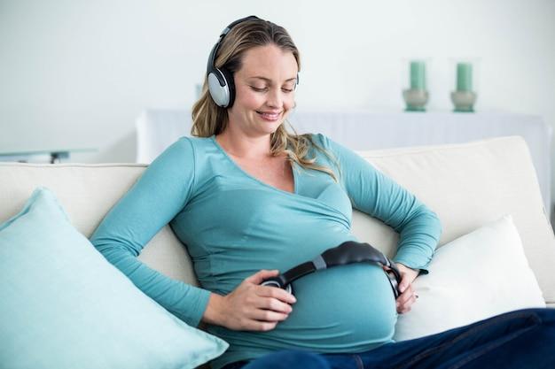 Mulher grávida, escutar música, com, fones, ligado, barriga, sofá