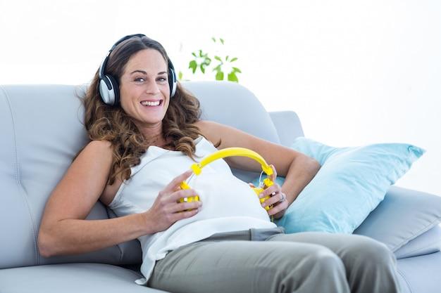 Mulher grávida, escutar música, em, sala de estar