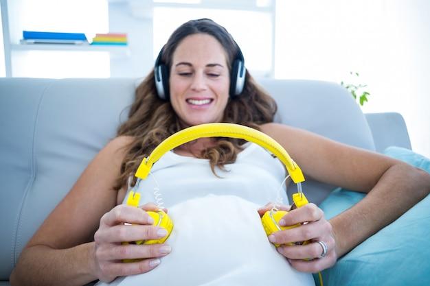 Mulher grávida, escutar música, ligado, sofá