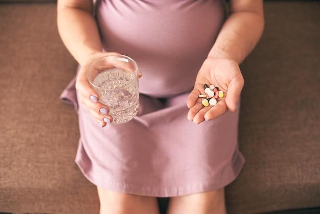 Mulher grávida esperando bebê e tomando vitaminas