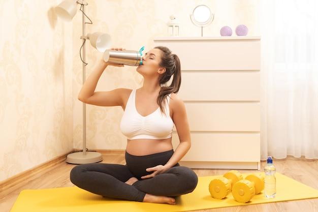 Mulher grávida está bebendo batido de proteína após o treino de fitness em casa