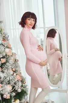 Mulher grávida está esperando o natal perto da árvore de natal.
