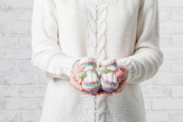 Mulher grávida está segurando sapatos pequenos para o bebê por nascer