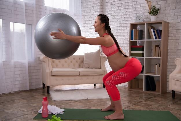 Mulher grávida está treinando a barriga com bola em casa