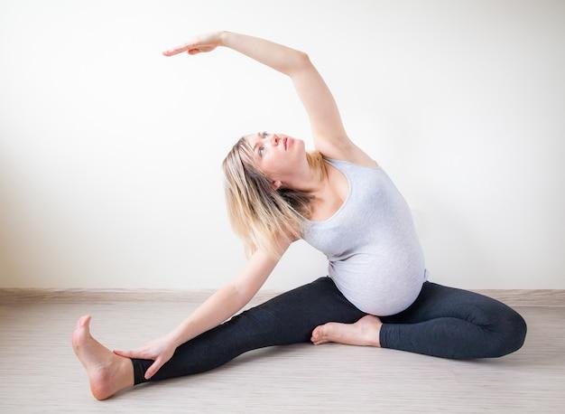Mulher grávida, esticando os braços e pernas