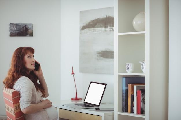 Mulher grávida falando no celular na sala de estudos