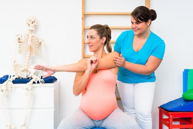 Mulher grávida faz exercícios de alongamento com fisioterapeuta