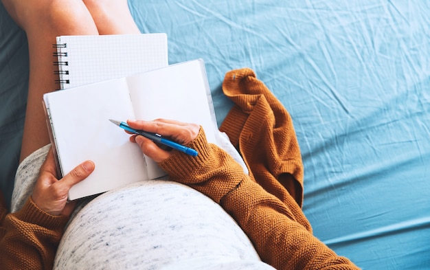 Mulher grávida fazendo anotações e olhando documentos médicos