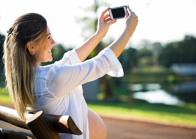 Mulher grávida fazendo autorretrato usando smartphone
