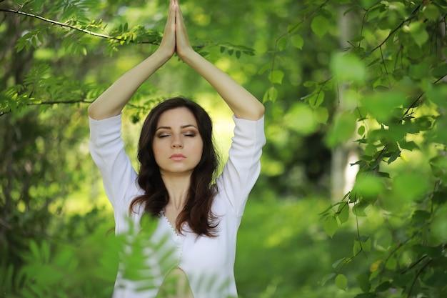 Mulher grávida fazendo exercícios de ioga na natureza no verão