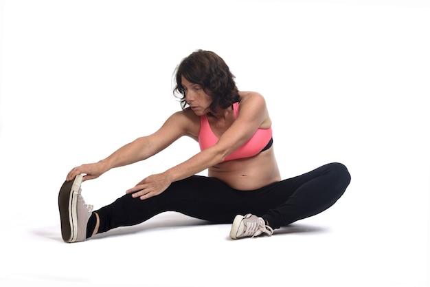 Mulher grávida fazendo exercícios de solo em fundo branco