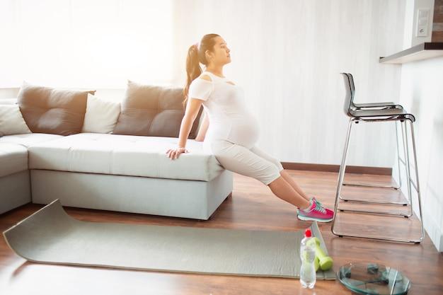 Mulher grávida fazendo exercícios em casa usando um sofá.