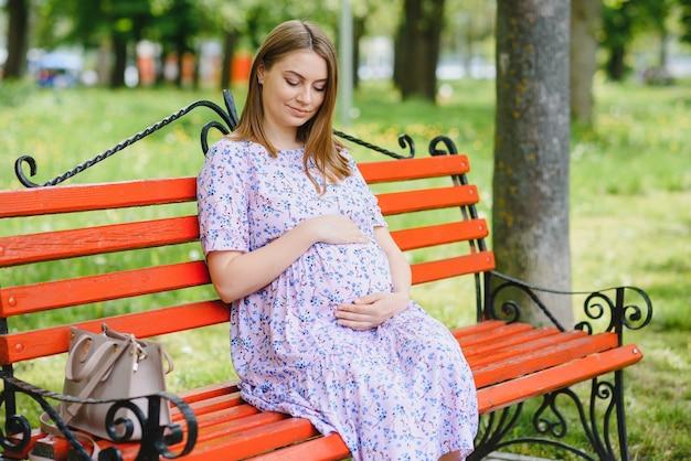 Mulher grávida fazendo ioga no parque. sentado na grama.