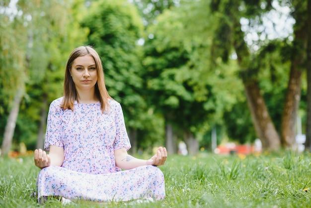Mulher grávida fazendo ioga no parque