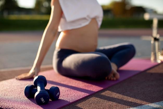 Mulher grávida fazendo ioga sozinha ao ar livre