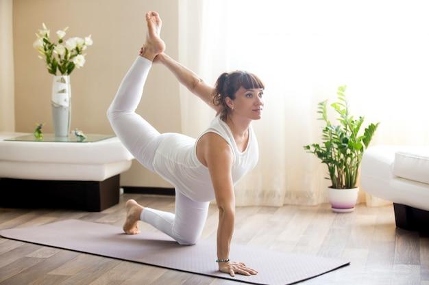 Mulher grávida fazendo pose de yoga de pássaro-cão em casa