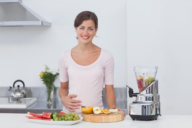 Mulher gravida fazendo um coquetel de frutas