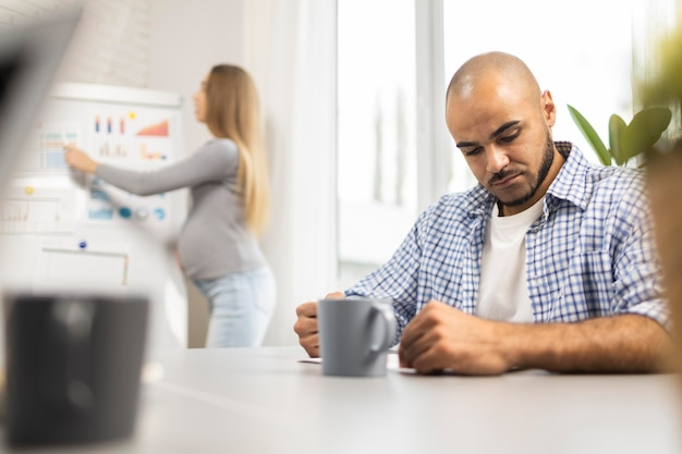Mulher grávida fazendo uma apresentação enquanto um colega de trabalho ouve