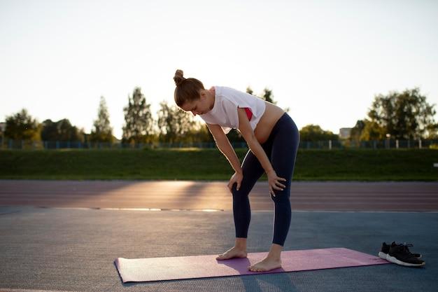 Mulher grávida fazendo uma pausa nos exercícios ao ar livre