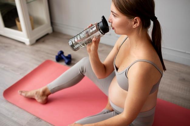 Mulher grávida fazendo uma pausa nos exercícios em casa