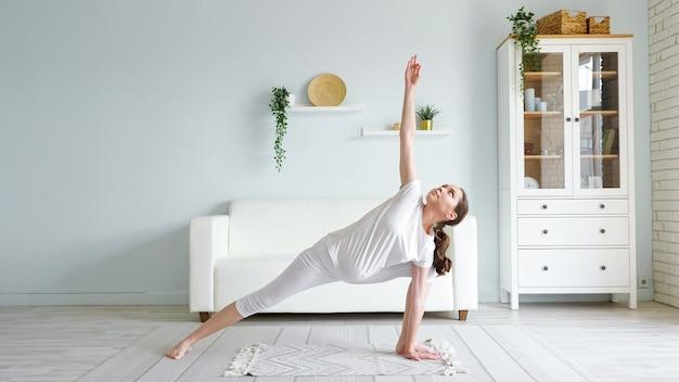 Mulher grávida fazendo utthita parsvakonasana no chão de casa