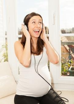 Mulher gravida feliz cantando e ouvindo música