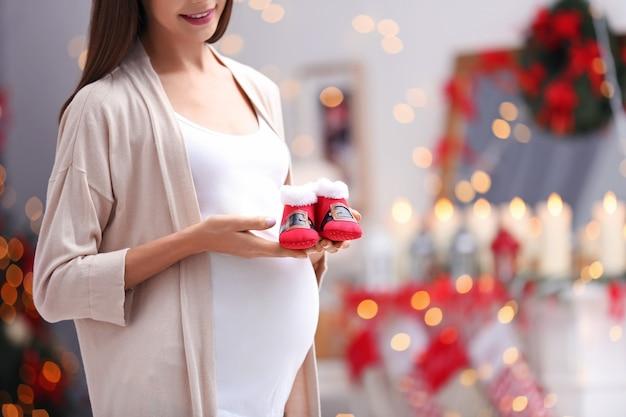 Mulher grávida feliz com botinhas de bebê em quarto decorado para o natal