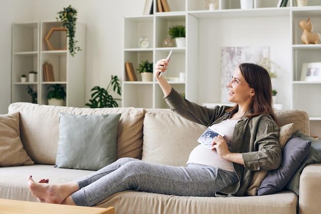 Mulher grávida feliz com foto ultrassônica de seu bebê fazendo selfie na frente da câmera do smartphone enquanto está sentado no sofá da sala de estar