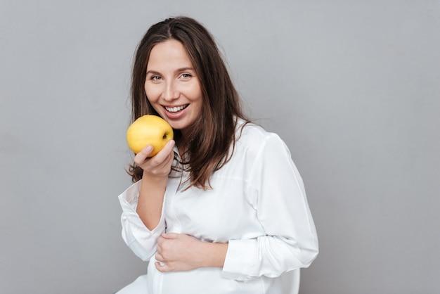 Mulher grávida feliz com maçã olhando para a câmera isolada de fundo cinza