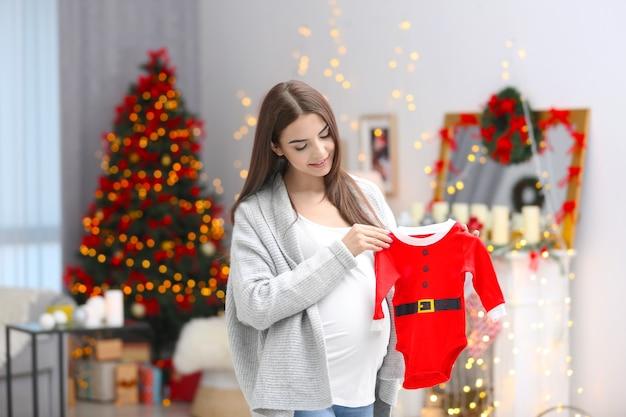 Mulher grávida feliz com roupa de bebê de papai noel em quarto decorado para o natal
