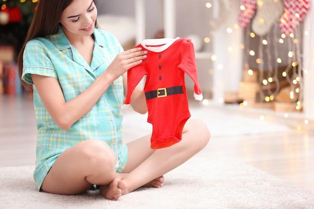 Mulher grávida feliz com roupa de bebê de papai noel sentada no chão em casa