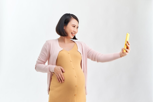 Mulher grávida feliz com smartphone tirando selfie sobre branco