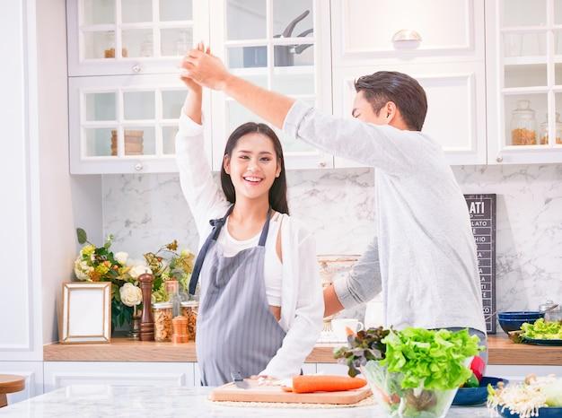 Mulher grávida feliz dançando com o marido na cozinha