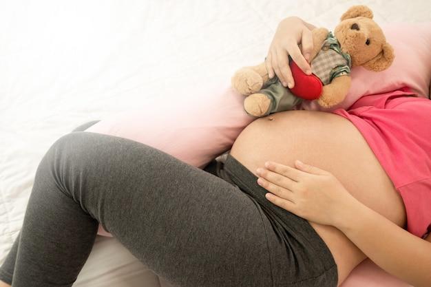 Mulher grávida feliz e bebê à espera.