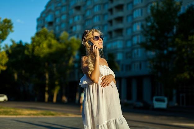 Mulher grávida feliz e caucasiana ligando para smartphone em streen na cidade