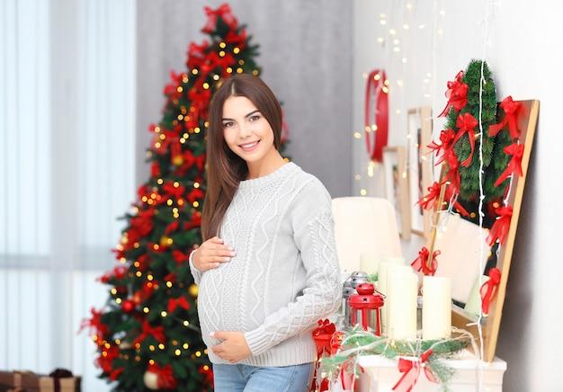 Mulher grávida feliz em quarto decorado para o natal