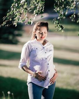 Mulher grávida feliz olhando para a barriga