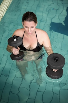 Mulher gravida feliz que exercita na associação com pesos no centro do lazer