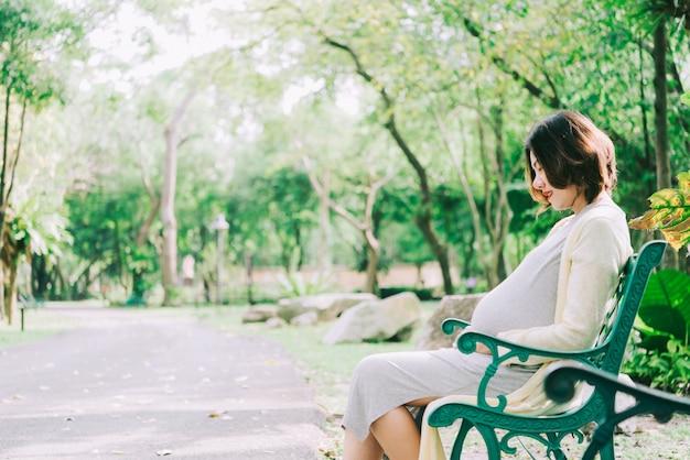Mulher gravida feliz que relaxa fora no parque ao ar livre