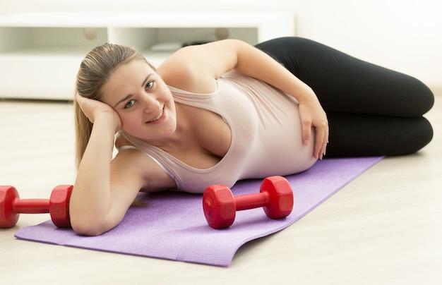 Mulher grávida feliz relaxando no colchonete após o exercício