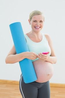 Mulher grávida feliz segurando o colchonete, enviando uma mensagem de texto